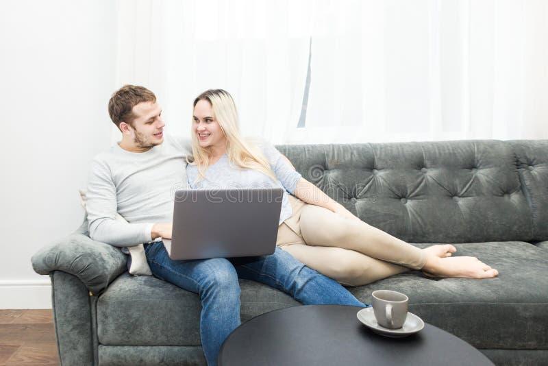 Νέο όμορφο ζεύγος που στηρίζεται στο σε απευθείας σύνδεση βίντεο καναπέδων και προσοχής από ένα lap-top στο καθιστικό στοκ εικόνα με δικαίωμα ελεύθερης χρήσης