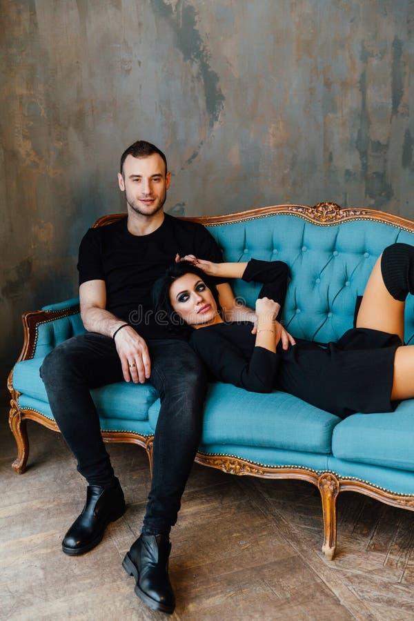 Νέο όμορφο ζεύγος στα σκοτεινά ενδύματα σε έναν τυρκουάζ εκλεκτής ποιότητας καναπέ στοκ εικόνες