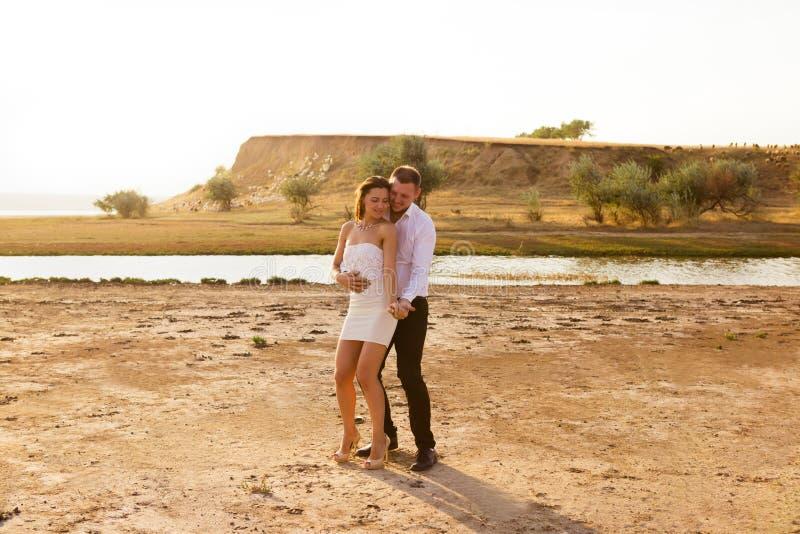 Νέο όμορφο ζεύγος στον άσπρο χορό στο υπόβαθρο του ήλιου στοκ φωτογραφίες