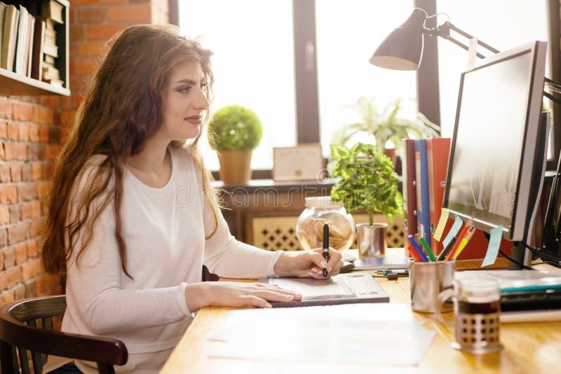 Νέο όμορφο θηλυκό desiner ή γραφικός καλλιτέχνης στο χώρο εργασίας στο γραφείο ύφους σοφιτών στοκ φωτογραφίες