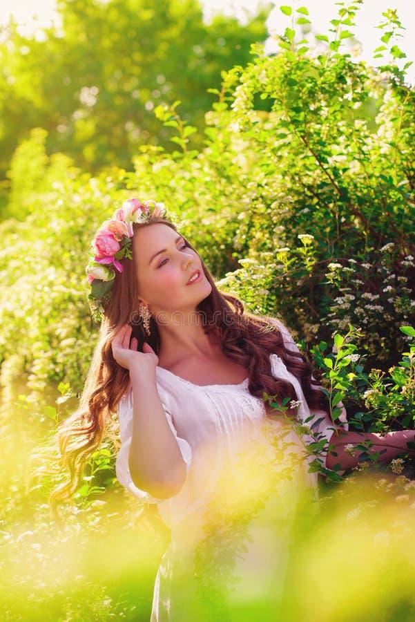 Νέο όμορφο κορίτσι με μακρυμάλλη στο floral στεφάνι την άνοιξη στοκ εικόνες