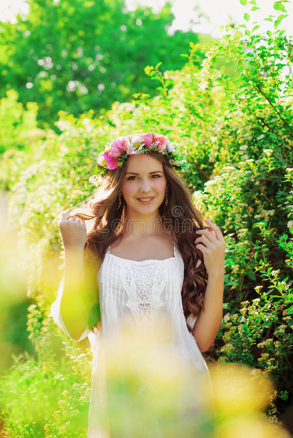 Νέο όμορφο κορίτσι με μακρυμάλλη στο floral στεφάνι την άνοιξη στοκ φωτογραφία με δικαίωμα ελεύθερης χρήσης
