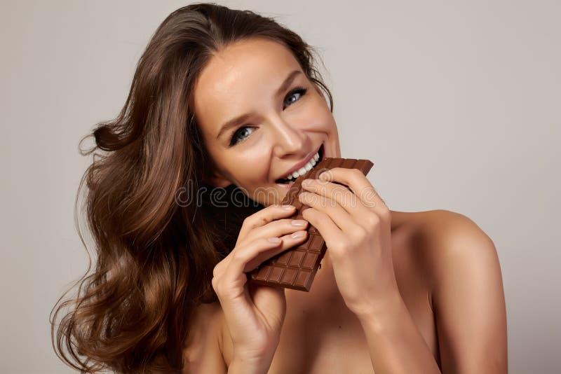 Νέο όμορφο κορίτσι με τη σκοτεινή σγουρή τρίχα, τους γυμνούς ώμους και το λαιμό, που κρατούν έναν φραγμό σοκολάτας για να απολαύσ στοκ φωτογραφία με δικαίωμα ελεύθερης χρήσης