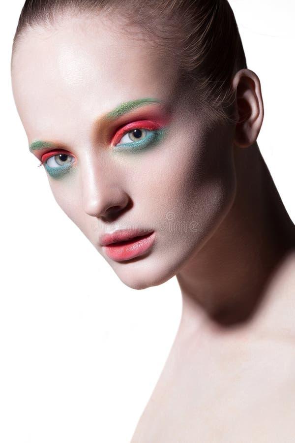 Νέο όμορφο κορίτσι με τη χρωματισμένη σύνθεση στοκ εικόνα