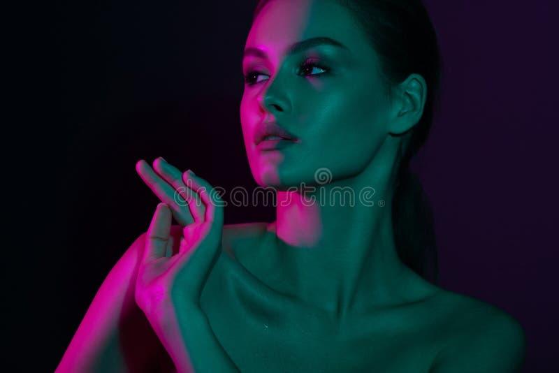 Νέο όμορφο κορίτσι με τον πορφυρό και πράσινο φωτισμό νέου στοκ φωτογραφίες