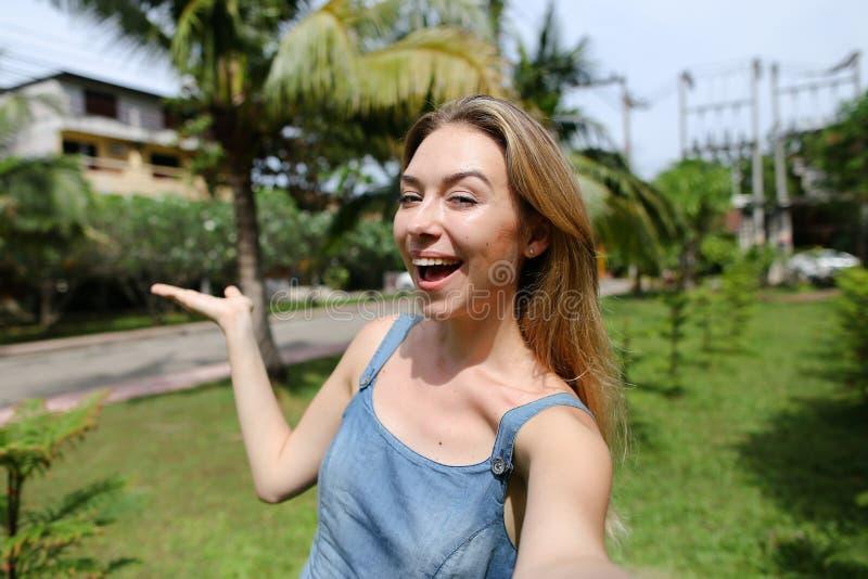 Νέο όμορφο κορίτσι που κάνει την τηλεοπτική κλήση από το smartphone κοντά στους φοίνικες στο υπόβαθρο στοκ εικόνα