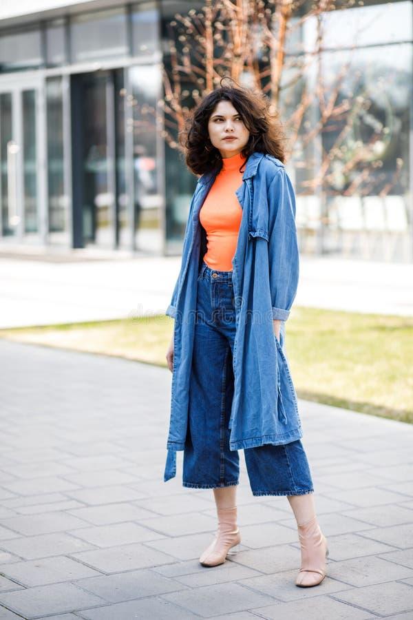 Νέο όμορφο κορίτσι που περπατά στην οδό, που ντύνεται στα τζιν και το πουκάμισο τζιν Εργάσιμες μέρες σπουδαστών στοκ εικόνες