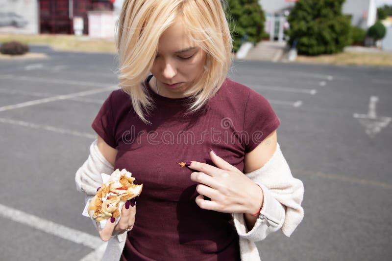 Νέο όμορφο κορίτσι που τρώει το χοτ-ντογκ στο χώρο στάθμευσης στοκ φωτογραφία με δικαίωμα ελεύθερης χρήσης