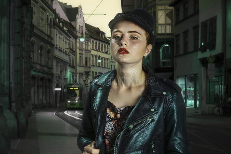 Νέο όμορφο κορίτσι σε μια ΚΑΠ και ένα σακάκι δέρματος στην οδό μιας ευρωπαϊκής πόλης νύχτας στοκ εικόνα με δικαίωμα ελεύθερης χρήσης