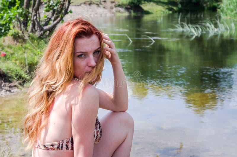 Νέο όμορφο κορίτσι σε μια συνεδρίαση κοστουμιών λουσίματος στην τράπεζα της θερινής ηλιόλουστης ημέρας ποταμών στοκ φωτογραφίες