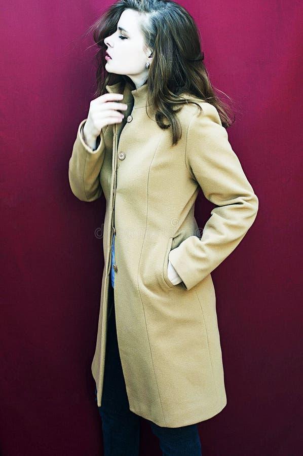 Νέο όμορφο κορίτσι στο γαλακτοκομικό παλτό burgundy στο υπόβαθρο στοκ φωτογραφίες