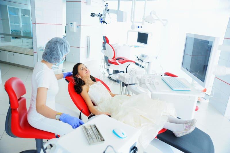 Νέο όμορφο κορίτσι στο οδοντικό γραφείο Ο οδοντίατρος των παιδιών εξετάζει τα δόντια σε ένα παιδί στοκ φωτογραφίες