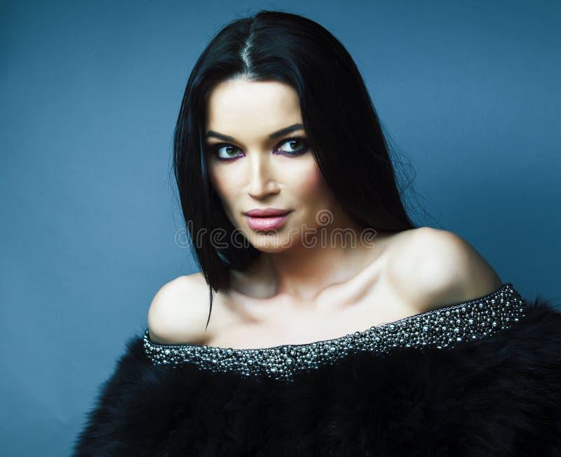 Νέο όμορφο κορίτσι brunette με την τοποθέτηση μόδας makeup κομψή στο παλτό γουνών με το κόσμημα στο μπλε υπόβαθρο, τρόπος ζωής στοκ εικόνα με δικαίωμα ελεύθερης χρήσης