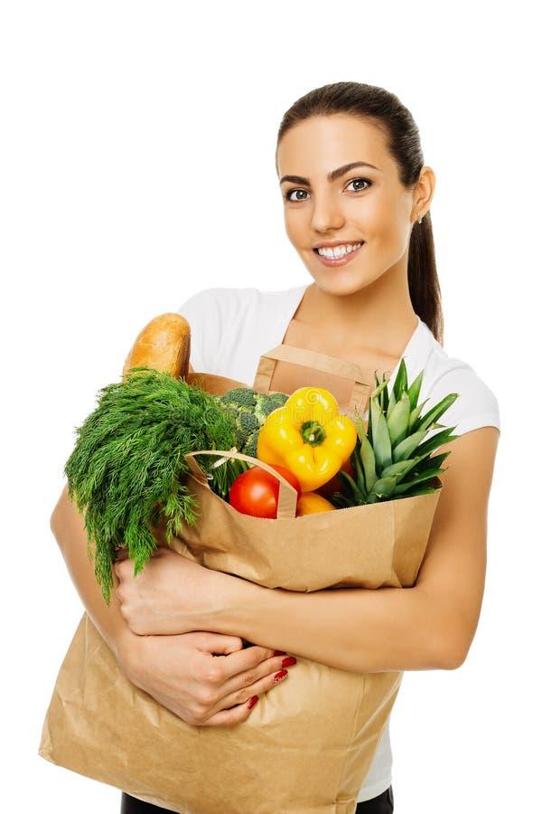 Νέο όμορφο κορίτσι brunette που κρατά μια συσκευασία με τα τρόφιμα, φρέσκα φρούτα και λαχανικά η ανασκόπηση απομόνωσε το λευκό στοκ φωτογραφίες
