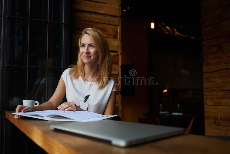 Νέο όμορφο κορίτσι hipster με την καλή συνεδρίαση διάθεσης με το μεγάλο σημειωματάριο στη καφετερία κατά τη διάρκεια του χρόνου α στοκ φωτογραφίες