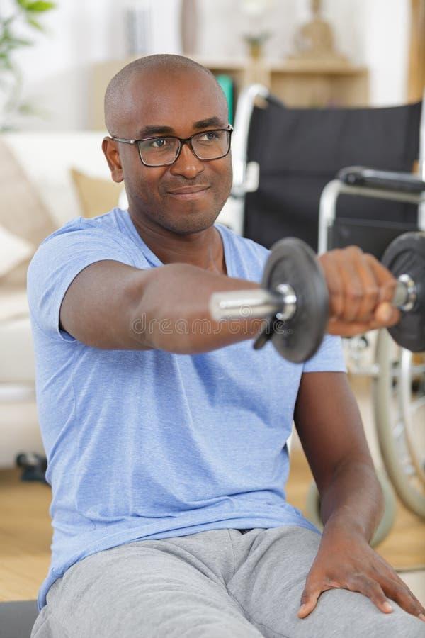 Νέο όμορφο με ειδικές ανάγκες παραπληγικό άτομο στην αναπηρική καρέκλα που κάνει τον αθλητισμό αποκατάστασης στοκ εικόνες με δικαίωμα ελεύθερης χρήσης