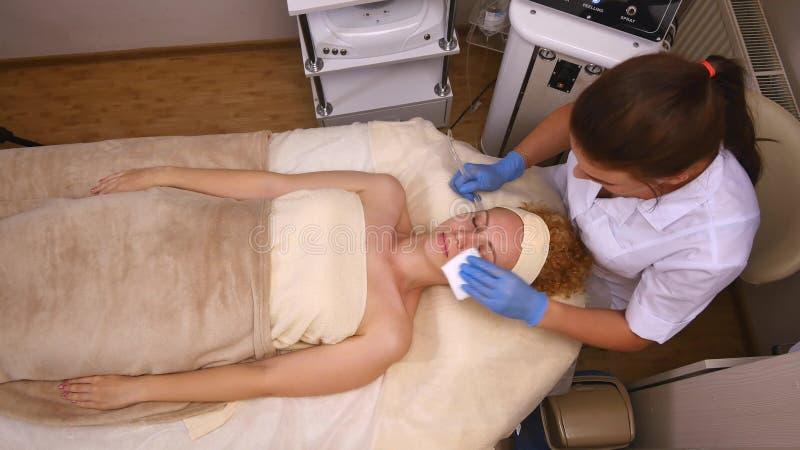 Νέο όμορφο να βρεθεί γυναικών στον κλινικό πίνακα, το cosmetologist της κάνει ένα του προσώπου μασάζ ηλεκτρο-υποκίνησης στοκ φωτογραφίες