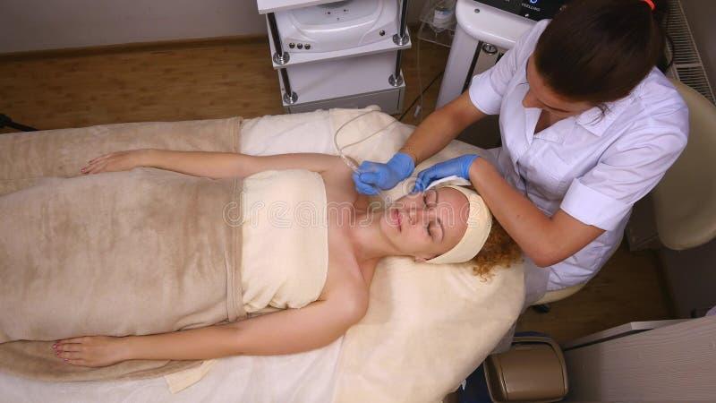 Νέο όμορφο να βρεθεί γυναικών στον κλινικό πίνακα, το cosmetologist της κάνει ένα του προσώπου μασάζ ηλεκτρο-υποκίνησης στοκ εικόνα