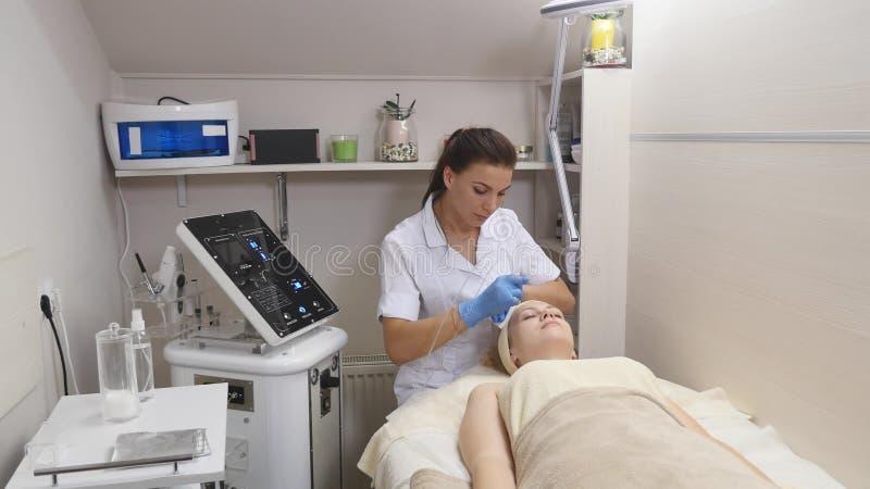 Νέο όμορφο να βρεθεί γυναικών στον κλινικό πίνακα, το cosmetologist της κάνει ένα του προσώπου μασάζ ηλεκτρο-υποκίνησης στοκ εικόνα με δικαίωμα ελεύθερης χρήσης