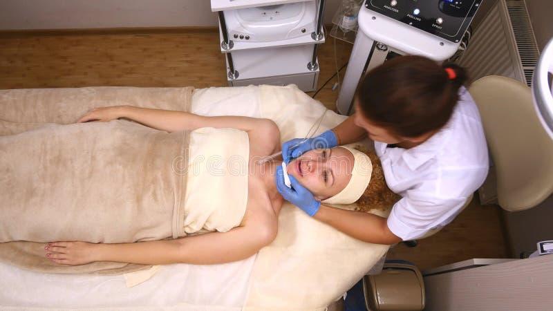 Νέο όμορφο να βρεθεί γυναικών στον κλινικό πίνακα, το cosmetologist της κάνει ένα του προσώπου μασάζ ηλεκτρο-υποκίνησης στοκ εικόνες