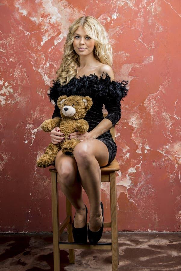 Νέο όμορφο ξανθό κορίτσι σε ένα μαύρο φόρεμα κοκτέιλ στοκ εικόνες