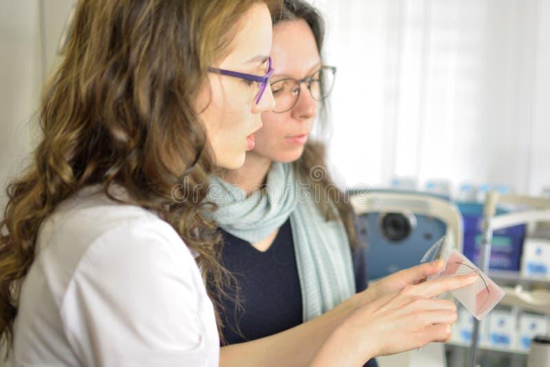 Νέο όμορφο πλαίσιο γυαλιών ματιών συναρμολογήσεων γυναικών υπομονετικό με optometrist οφθαλμολόγων τον οπτικό στοκ φωτογραφίες