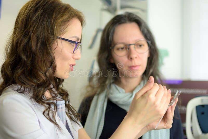 Νέο όμορφο πλαίσιο γυαλιών ματιών συναρμολογήσεων γυναικών υπομονετικό με optometrist οφθαλμολόγων τον οπτικό στοκ φωτογραφία με δικαίωμα ελεύθερης χρήσης