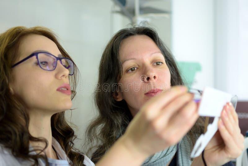 Νέο όμορφο πλαίσιο γυαλιών ματιών συναρμολογήσεων γυναικών υπομονετικό με optometrist οφθαλμολόγων τον οπτικό στοκ εικόνα με δικαίωμα ελεύθερης χρήσης
