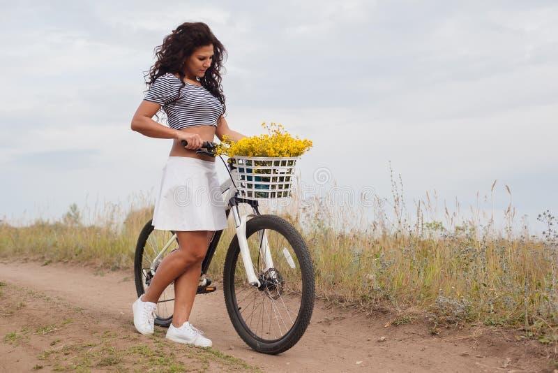 Νέο όμορφο ποδήλατο womanon στην επαρχία στοκ φωτογραφία