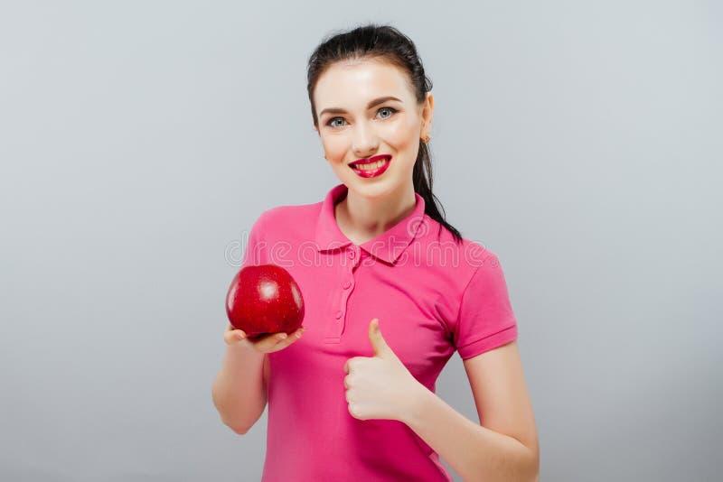 Νέο όμορφο προκλητικό κορίτσι με τη σκοτεινή σγουρή τρίχα, τους γυμνούς ώμους και το λαιμό, που κρατούν το μεγάλο κόκκινο μήλο γι στοκ εικόνα με δικαίωμα ελεύθερης χρήσης
