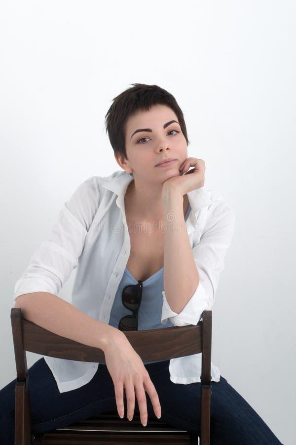 Νέο όμορφο προκλητικό χαμογελώντας κορίτσι στη συνεδρίαση πουκάμισων στην καρέκλα που απομονώνεται στο άσπρο υπόβαθρο, που εξετάζ στοκ φωτογραφία