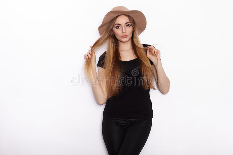 Νέο όμορφο πρότυπο μόδας γυναικών στη μαύρη τοποθέτηση καπέλων μπλουζών καθιερώνουσα τη μόδα στο στούντιο στο άσπρο κλίμα στοκ φωτογραφίες