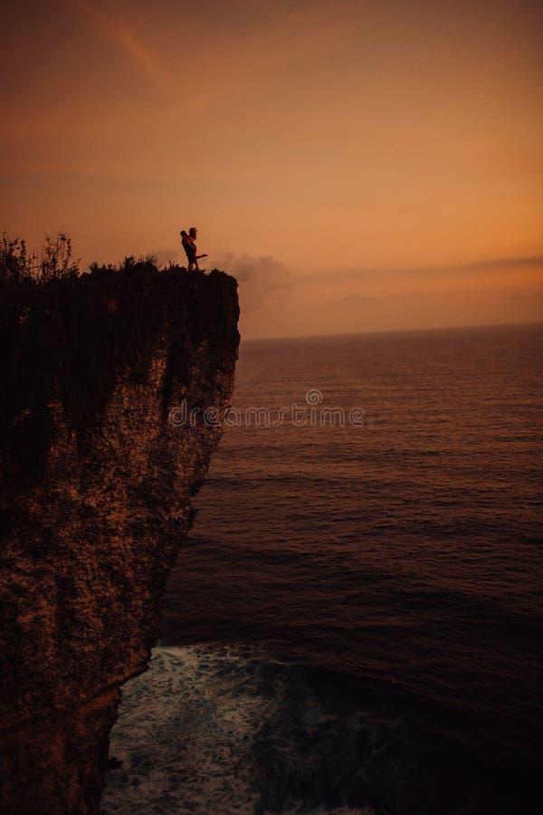 Νέο όμορφο φίλημα ζευγών στο ηλιοβασίλεμα κοντά στη θάλασσα, σκιαγραφία στοκ φωτογραφία με δικαίωμα ελεύθερης χρήσης