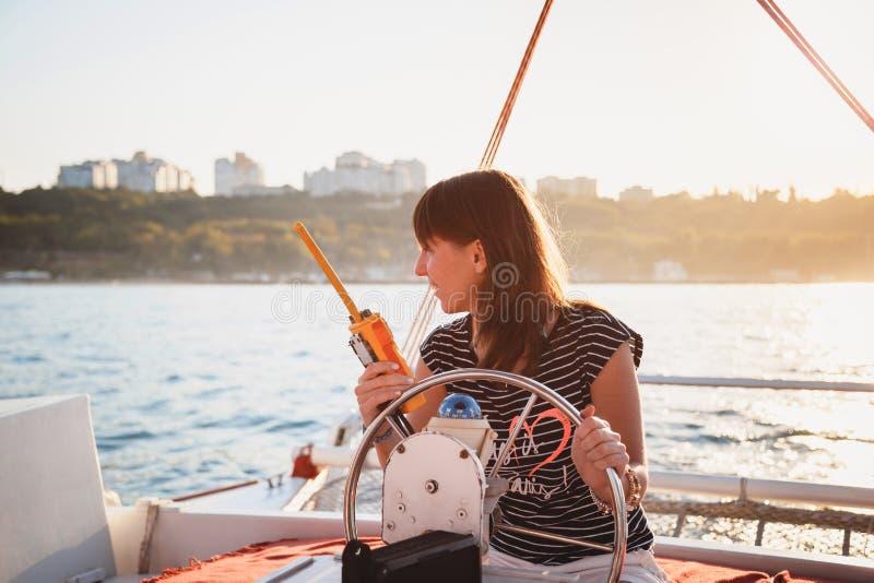 Νέο όμορφο χαμογελώντας κορίτσι στο ριγωτό πουκάμισο και τα άσπρα σορτς που οδηγούν το γιοτ πολυτέλειας με walkie-talkie στα χέρι στοκ εικόνα