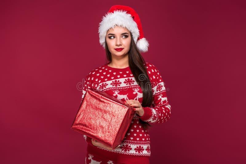 Νέο όμορφο χριστουγεννιάτικο δώρο εκμετάλλευσης γυναικών στα χέρια της στο κόκκινο υπόβαθρο στούντιο στοκ φωτογραφίες