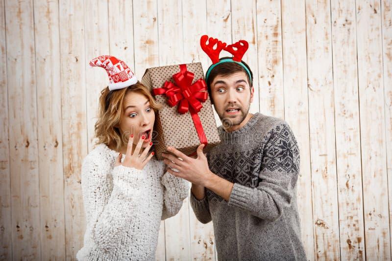 Νέο όμορφο δώρο Χριστουγέννων εκμετάλλευσης ζευγών πέρα από το ξύλινο υπόβαθρο στοκ εικόνες