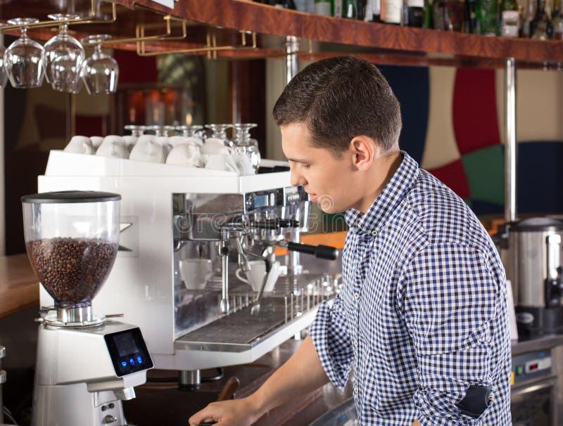 Νέο όμορφο barista που κατασκευάζει τον καφέ που χρησιμοποιεί τον εμπορικό βαθμό coff στοκ εικόνες με δικαίωμα ελεύθερης χρήσης