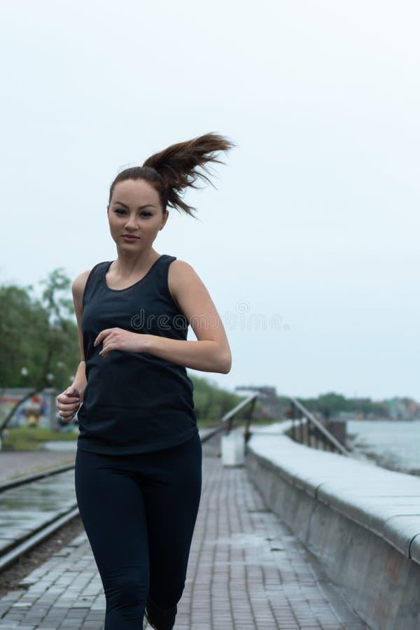 Νέο όμορφο redhead κορίτσι με τις φακίδες που περιλαμβάνονται στον αθλητισμό Τρεξίματα κατά μήκος της ακτής r στοκ φωτογραφίες με δικαίωμα ελεύθερης χρήσης
