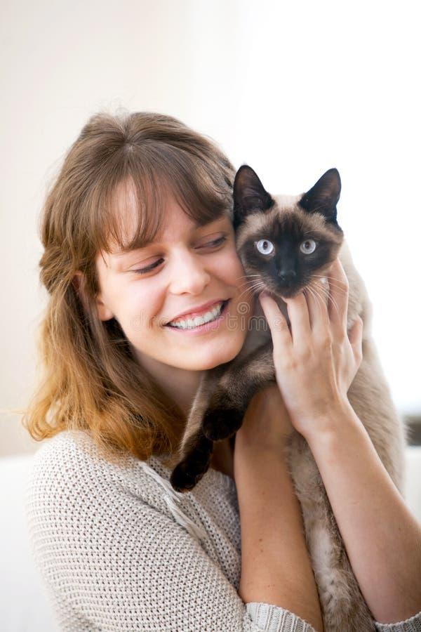νέο atractive κορίτσι που αγκαλιάζει τη γάτα της στοκ εικόνα με δικαίωμα ελεύθερης χρήσης