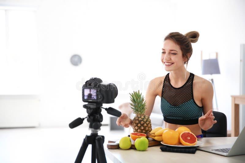 Νέο blogger με τα φρούτα που καταγράφουν το βίντεο στην κουζίνα στοκ φωτογραφία