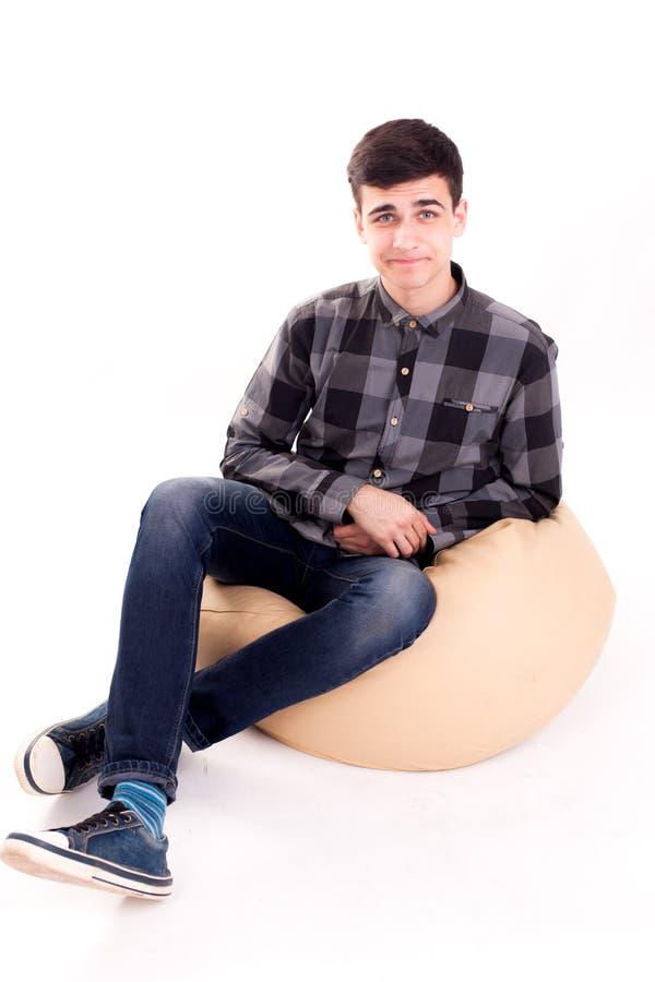 Νέο blogger στη μαλακή καρέκλα που καθιστά το αστείο πρόσωπο απομονωμένο στοκ εικόνα
