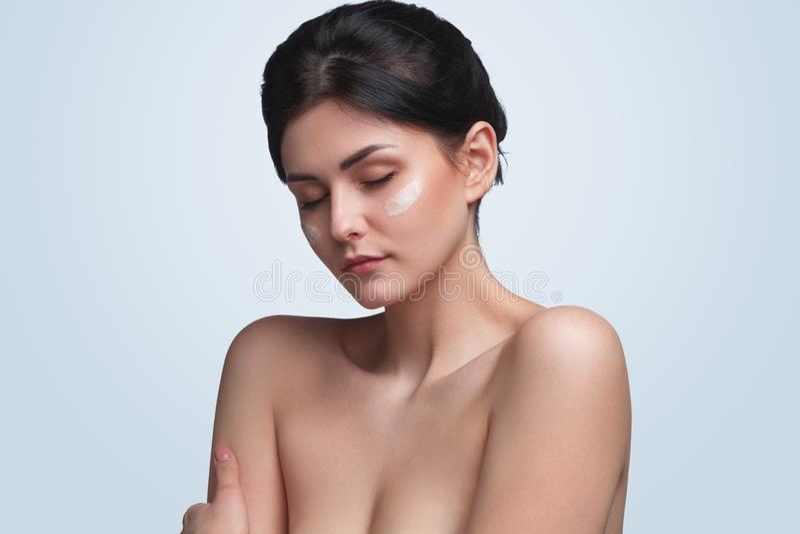 Νέο brunette με την κρέμα στα μάγουλα στοκ εικόνες
