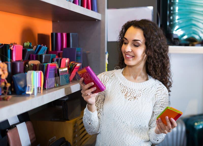 Νέο brunette που επιλέγει το πορτοφόλι με πολλά τμήματα στο κατάστημα στοκ φωτογραφία