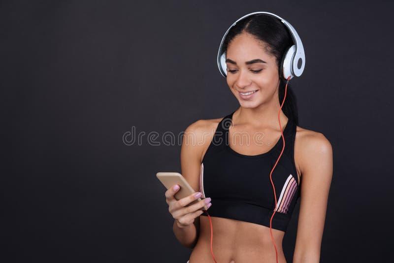 Νέο brunette χαμόγελου που φορά τα ακουστικά στοκ εικόνες