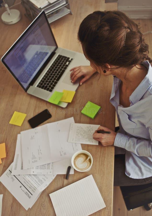 Νέο brunette χρησιμοποιώντας το lap-top ενώ στην εργασία στοκ εικόνες με δικαίωμα ελεύθερης χρήσης