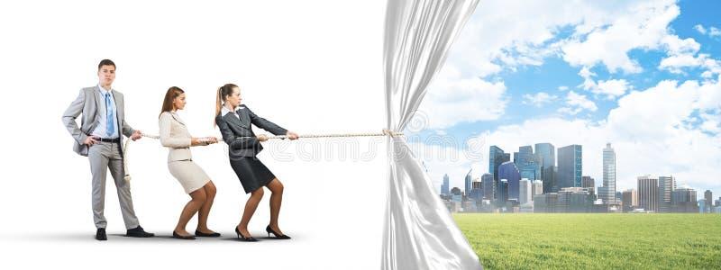 Νέο businesspeople που λειτουργεί στη συνεργασία και που τραβά το άσπρο έμβλημα διαφημίσεων στοκ φωτογραφία
