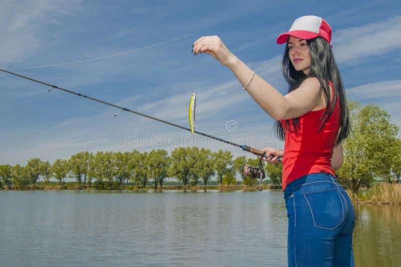 Νέο fisherwoman να προετοιμαστεί για την αλιεία Το κορίτσι με την αλιεία της ράβδου εξετάζει το θέλγητρο στοκ εικόνα με δικαίωμα ελεύθερης χρήσης