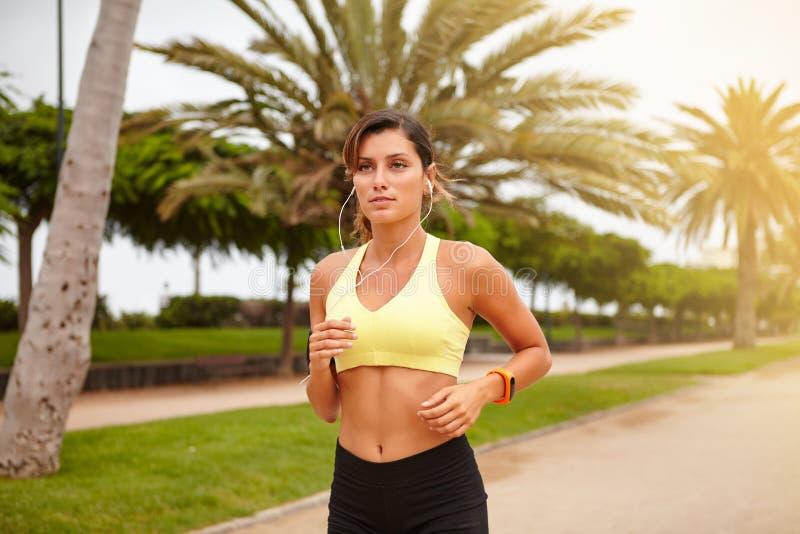 Νέο jogger που ακούει τη μουσική τρέχοντας στοκ εικόνες