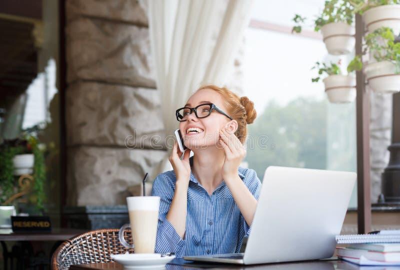Νέο redhead θηλυκό freelancer υπαίθρια που εργάζεται με το lap-top στοκ εικόνες