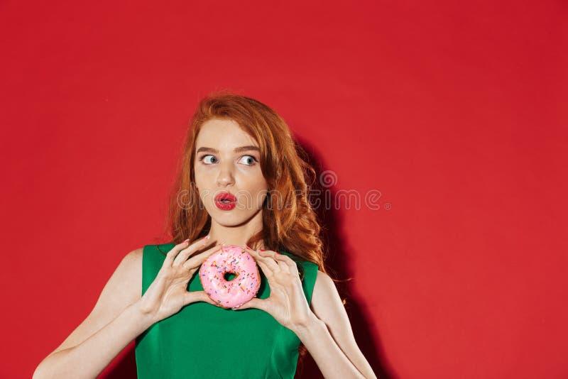 Νέο redhead χαριτωμένο κορίτσι στο πράσινο φόρεμα με doughnut στοκ εικόνες